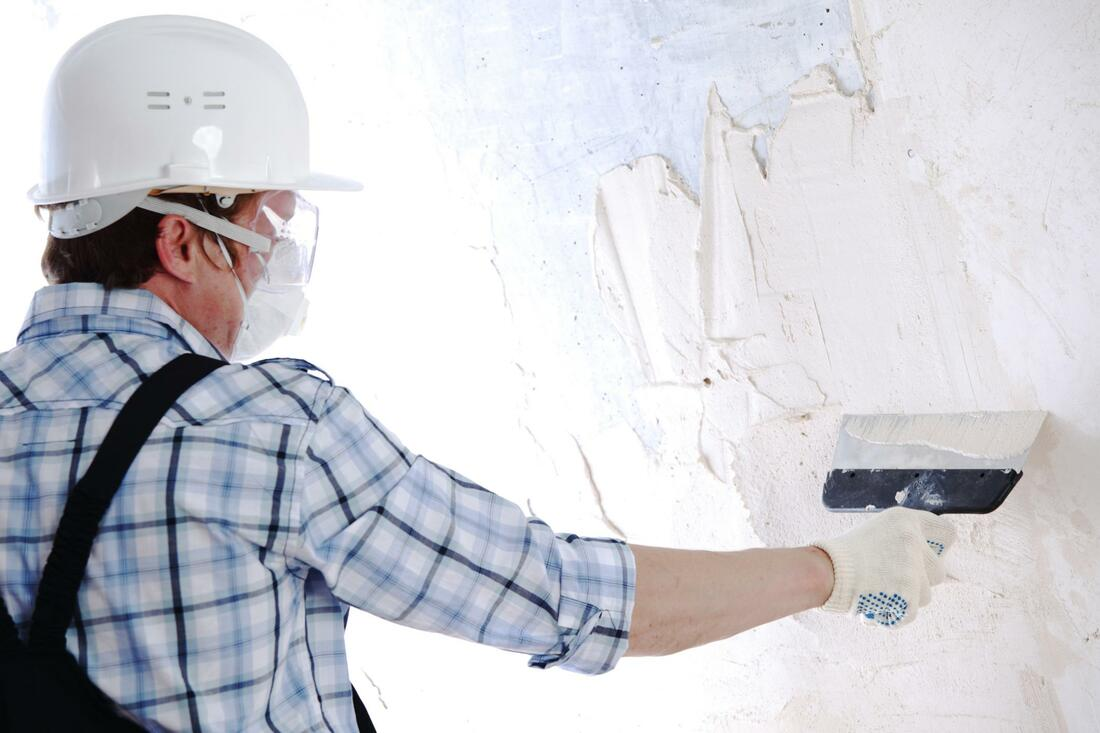 Male worker putting plaster on wall